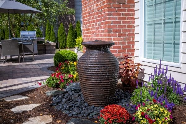 An urn turned water feature cascades into a bed of rock in a landscape bed.