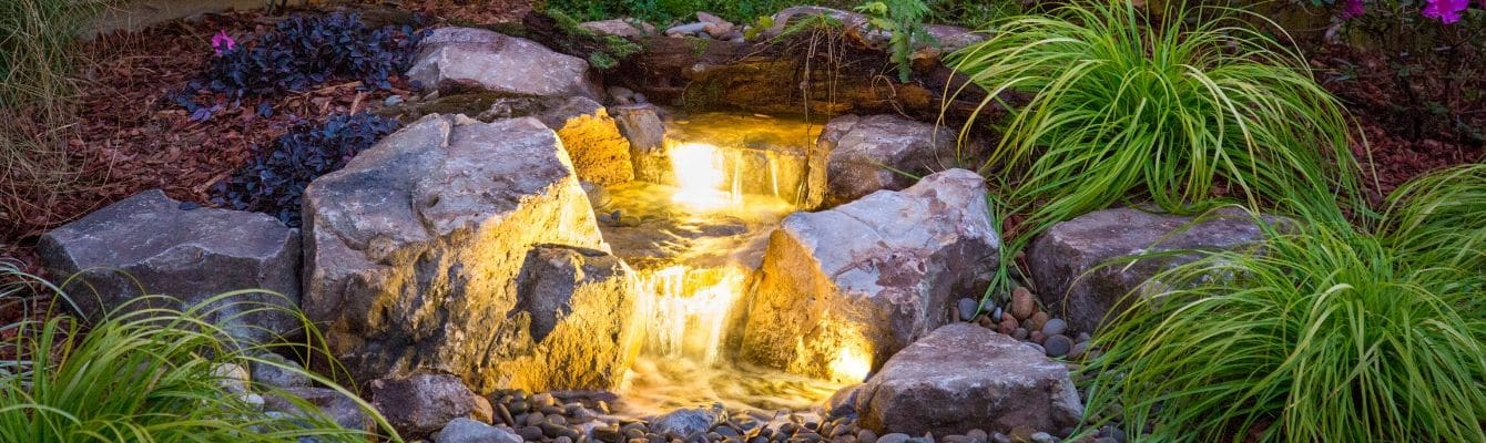 A lighted water feature that cascades through the landscape bed.