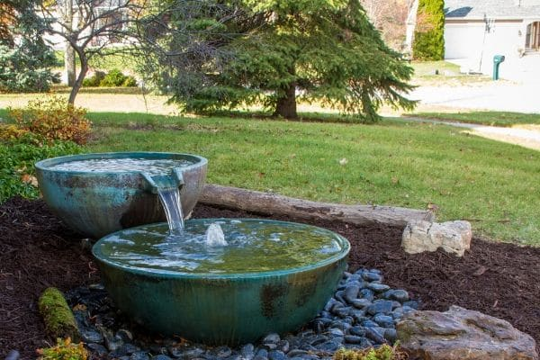 A water feature placed in a landscape bed.