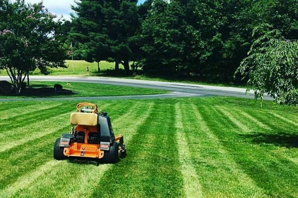 Professional mower parked on lawn in process of being mowed.