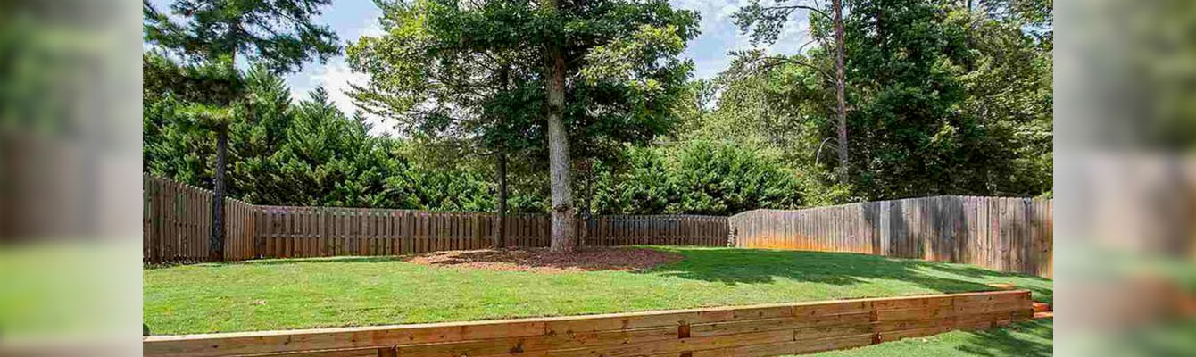 The back yard of a residential property with a retaining wall, fence, lush lawn, and beautiful trees.