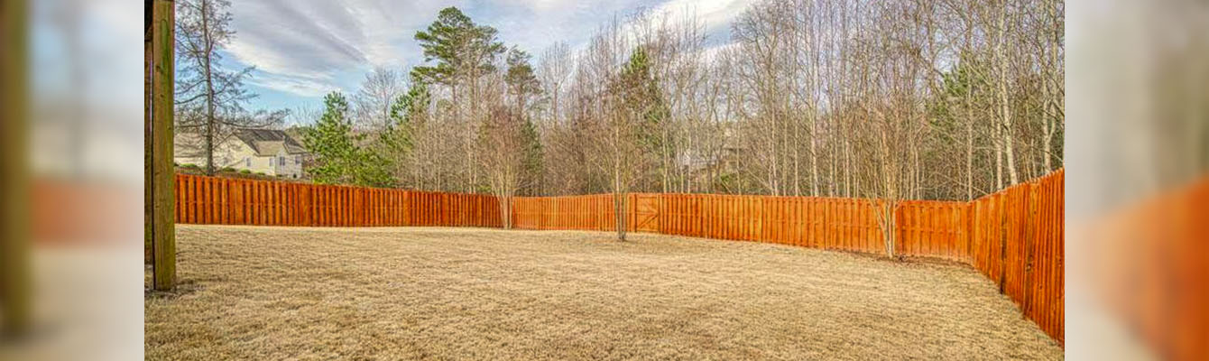 The backyard of a residential property with a tall wooden fence and trees beyond the fence.