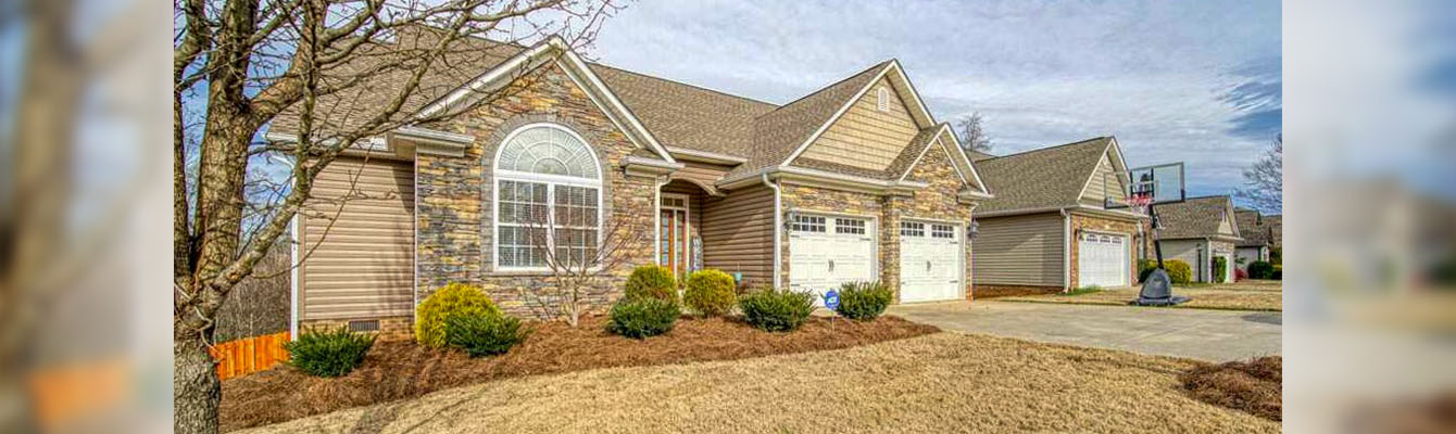 A residential property with a nicely manicured lawn and well maintained flower beds.